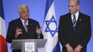 رئيس السلطة الفلسطينية محمود عباس، يسار،  ورئيس الوزراء الإسرائيلي إيهود أولمرت، يمين، يقف بجانبه خلال مؤتمر صحافي في قصر الإليزيه في بارس، 13 يوليو، 2008. (AP Photo/Jacques Brinon)