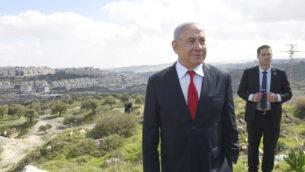 رئيس الوزراء بنيامين نتنياهو يقف في موقع يطل على حي هار حوما بالقدس الشرقية، اثناء الاعلان عن بناء حي جديد في الحي، 20 فبراير 2020. (Debbie Hill/Pool via AP)