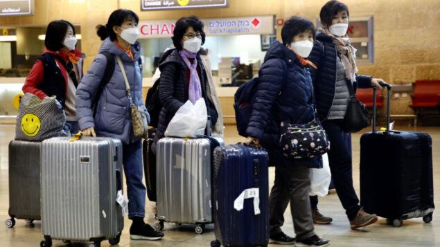 سائحون من كوريا يرتدون أقنعة واقية أثناء انتظار رحلتهم، في مطار بن غوريون بالقرب من تل أبيب، 23 فبراير 2020. (AP Photo / Ariel Schalit)