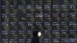 صورة توصيحية: امرأة تسير امام لوحة أسهم إلكترونية تعرض مؤشر Nikkei 225 الياباني في إحدى شركات الأوراق المالية في طوكيو، 25 فبراير 2020 (AP / Eugene Hoshiko)