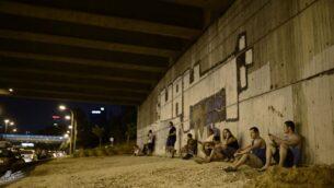صورة توضيحية: إسرائيليون يختبئون في اعقاب انطلاق صفارات الإنذار المحذرة من الصواريخ القادمة في تل أبيب، في اليوم الخامس من عملية الجرف الصامد، 12 يوليو 2014 (Tomer Neuberg/Flash90)