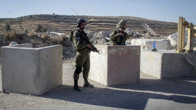 صورة توضيحية: جنود إسرائيليون في حاجز بالقرب من مدينة الخليل في الضفة الغربية، 2 يوليو 2016 (Wisam Hashlamoun/Flash90)