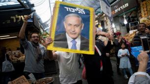 أحد مؤيدي حزب الليكود يحمل ملصقًا يظهر رئيس الوزراء بنيامين نتنياهو في سوق محانيه يهودا في القدس، 7 أبريل 2019. (Yonatan Sindel / Flash90)