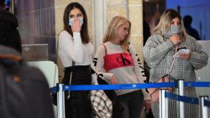 أشخاص يضعون الأقنعة في مطار بن غوريون الدولي، في أعقاب التقارير عن فيروس كورونا القاتل، الذي بدأ في الصين وانتشر في جميع أنحاء العالم، 2 فبراير، 2020. (Avshalom Shoshani/Flash90)
