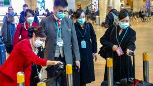 أشخاص يرتدون أقنعة الوجه في مطار بن غوريون الدولي في اعقاب تقارير عن فيروس كورونا القاتل، الذي نشأ في الصين، وانتشر في جميع أنحاء العالم. 17 فبراير 2020. (Avshalom Shoshani/Flash90)