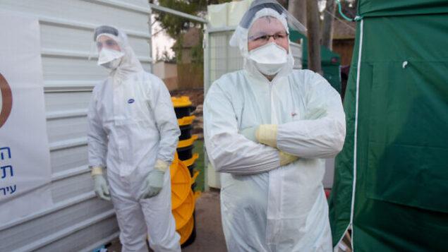 عمال داخل مبنى في المركز الطبي 'شيبا' الذي تم تجهيزه لاستقبال الإسرائيليين الذين كانوا في حجر صحي على متن سفينة 'دايموند يرينسس' السياحية في اليابان بسبب انتشار فيروس كورونا، 20 فبراير، 2020. (Avshalom Sassoni/Flash90)