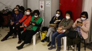 السياح الكوريون الجنوبيون المجبرون على مغادرة البلاد يرتدون أقنعة أثناء انتظارهم رحلنهم في منطقة معزولة في مطار بن غوريون الدولي، 24 فبراير 2020. (Flash90)