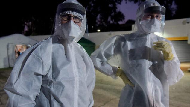 طاقم طبي في مستشفى تل هشومير في انتظار إسرائيليين سيتم إدخالهم في حجر صحي بسبب فيروس كورونا، 20  فبراير، 2020. (Avshalom Sassoni/Flash90)