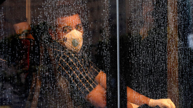 راكب يرتدي قناعًا وسط مخاوف من فيروس كورونا على متن حافلة في طهران، إيران، 23 فبراير 2020. (AP Photo / Ebrahim Noroozi)
