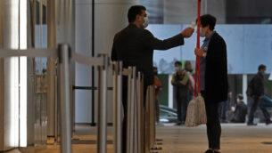 حارس أمن يرتدي قناع الوجه الواقي يقوم بفحص درجة حرارة امرأة تنظف وسط مخاوف من فيروس كورونا في هونغ كونغ، 14 فبراير 2020. (AP Photo / Vincent Yu)