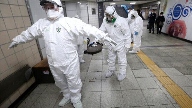 عمال يرتدون ملابس واقية يساعدون في تنظيف بدلات بعضهم البعض بعد تعقيمهم ضد فيروس كورونا في محطة مترو في سول، كوريا الجنوبية، 21  فبراير، 2020.  (AP Photo/Ahn Young-joon)