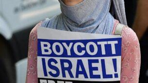 """صورة توضيحية: متظاهرة تحمل لافتة كُتب عليها """"مقاطعة إسرائيل، فلسطين حرة"""" خلال متظاهرة بمناسبة 'يوم القدس' في برلين، 9 يونيو، 2018.  (AFP PHOTO / Tobias SCHWARZ)"""