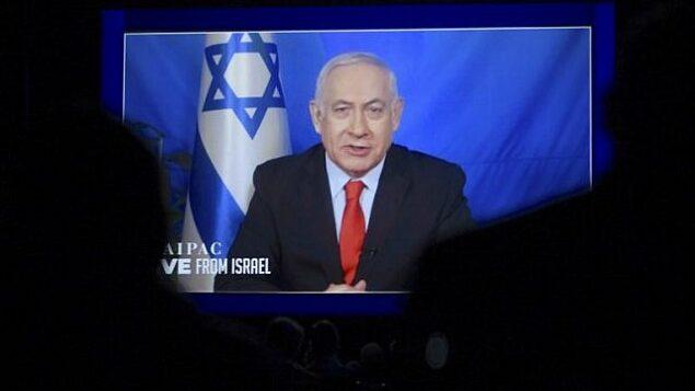 رئيس الوزراء بنيامين نتنياهو يتحدث من إسرائيل عبر رابط فيديو في المؤتمر السنوي لمنظمة إيباك في واشنطن، 26 مارس، 2019. ( Jim Watson/AFP)