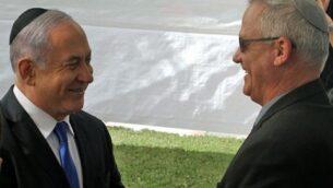 رئيس الوزراء بنيامين نتنياهو (يسار) ورئيس حزب 'أزرق أبيض'، بيني غانتس، يتصافحان خلال مراسم تذكارية لرئيس الدولة السابق شمعون بيرس في القدس، 19 سبتمبر، 2019 (GIL COHEN-MAGEN/AFP)