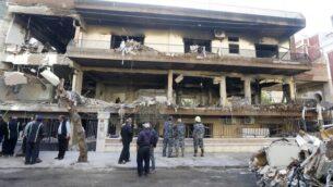 قوى الأمن وعمال البلدية خارج مبنى تم استهدافه في غارة جوية في حي المزة بالعاصمة السورية دمشق ليلا، 12 نوفمبر، 2019. (LOUAI BESHARA / AFP)