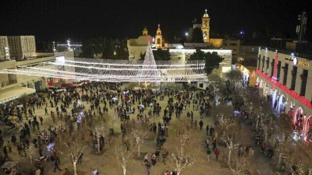 سياح وحجاج يزورون ساحة المهد خارج كنيسة المهد في مدينة بيت لحم بالضفة الغربية، 24 ديسمبر، 2019.  (HAZEM BADER / AFP)