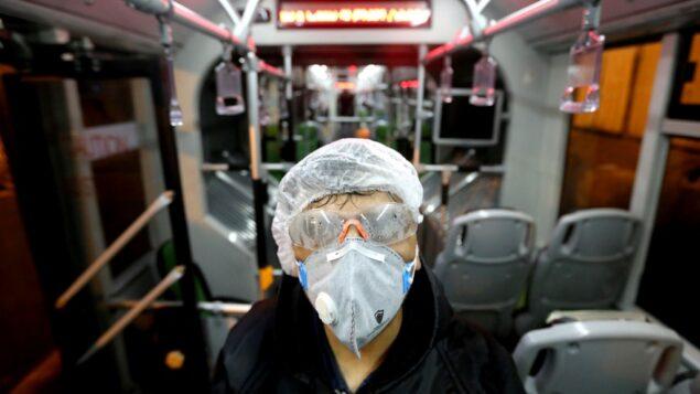 عامل من بلدية طهران يعقم حافلة لتجنب انتشار فيروس كورونا، 26 فبراير 2020 (ATTA KENARE / AFP)