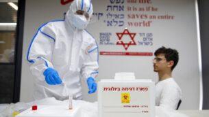 مسعف نجمة داود الحمراء يجري فحص لفيروس كورونا لمتطوع في مركز عمليات فيروس كورونا الوطني في كريات أونو، 26 فبراير 2020. (Jack Guez/AFP)