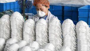 عاملة تنتج أقنعة الوجه في مصنع في هاندان بمقاطعة خبي بشمال الصين، 28 فبراير 2020 (STR / AFP / China OUT)