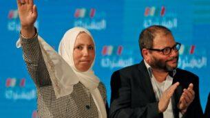 إيمان خطيب ياسين، السياسية الإسرائيلية العربية التي تمثل الفرع الجنوبي للحركة الإسلامية في تحالف القائمة المشتركة، ترفع يدها بينما تقف بجانب عوفر كاسيف، العضو اليهودي في القائمة ومرشح حزب الجبهة في التحالف، بينما يقفان امام أنصار القائمة في مقرهم الانتخابي في مدينة شفا عمرو بشمال إسرائيل، 2 مارس 2020 (Ahmad GHARABLI / AFP)
