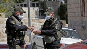 عنصران من قوى الأمن الفلسطينية يضعان قناعين ويقومان بتطهير أيدهما قرب فندق تم إغلاقه في بيت جالا، جنوب القدس، بعد تأكيد وجود إصابات بفيروس كورونا COVID-19، في 5 مارس، 2020. (Musa Al Shaer/AFP)