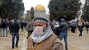 رجل فلسطيني يرتدي قناعا واقيا كإجراء حماية ضد فيروس كورنا COVID-19، يقف أمام قبة الصخرة في الحرم القدسي بالبلدة القديمة، قبل صلاة الجمعة،   6 مارس، 2020. (Ahmad Gharabli/AFP)