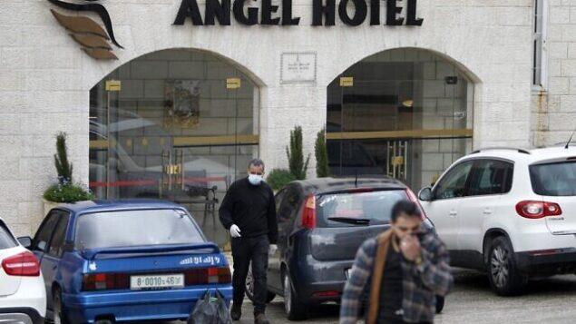 رجال فلسطينيون، أحدهم يضع قناعا واقيا، يغادرون فندق Angel في بيت مدينة لحم بالضفة الغربية قي بيت لحم، 6 مارس، 2020. (Musa Al Shaer/AFP)
