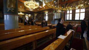 مجموعة صغيرة من المصلين تحضر قداس في كنيسة أرثوذكسية في بيت ساحور بالقرب من مدينة بيت لحم بالضفة الغربية، 8 مارس 2020. (Musa Al Shaer/AFP)