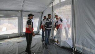 مسؤولون في وزارة الصحة الفلسطينية بالتعاون مع منظمة الصحة العالمية يقومون بإنشاء خيم خارجية لإجراء فحص طبي أولي لمن يُشتبه بإصابتهم بفيروس كورونا عند معبر رفح الحدودي مع مصر جنوبي قطاع غزة،  12 مارس، 2020.  (Said Khatib/AFP)