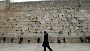 رجل يهودي متشدد يمشي أمام ناس يصلون عند حائط المبكى في البلدة القديمة بالقدس، 12 مارس 2020 (Emmanuel Dunand / AFP)