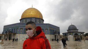 شاب فلسطيني يرتدي قناعا واقيا كإجراء حماية ضد فيروس كورنا COVID-19، يقف أمام قبة الصخرة في الحرم القدسي بالبلدة القديمة، 13 مارس، 2020. (Ahmad Gharabli/AFP)
