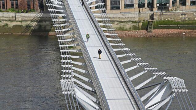 مشاة يعبرون جسر المشاة ميلينيوم الخالي  عبر نهر التيمز في لندن، في منتصف صباح يوم 17 مارس 2020 (JUSTIN TALLIS / AFP)