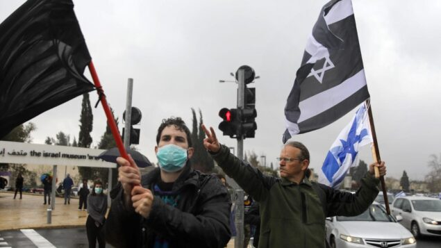 متظاهرون يلوحون بعلم أسود، علم إسرائيلي وعلم إسرائيلي بألوان مقلوبة، خارج الكنيست في القدس في 19 مارس 2020. الاحتجاج ضد القرار الأخير لرئيس الكنيست بإغلاق البرلمان لعدة أيام، وضد ما وُصف بـ'ضرر للديمقراطية الإسرائيلية' (MENAHEM KAHANA / AFP)