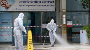 """رجال إطفاء إسرائيليون يقومون بإجراءات تعقيم عند مدخل المركزالطبي """"سوراسكي"""" في مدينة تل أبيب، 20 مارس، 2020. (Photo by JACK GUEZ / AFP)"""