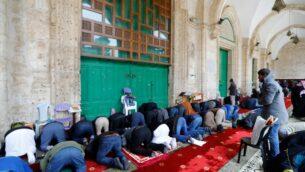 مسلمون فلسطينيون يجتمعون لأداء صلاة الجمعة أمام أبواب المسجد الأقصى في البلدة القديمة بالقدس، بعد أن أغلق رجال الدين أبواب المسجد وقبة الصخرة، في محاولة لوقف انتشار فيروس كورونا، 20 مارس 2020 (AHMAD GHARABLI / AFP)