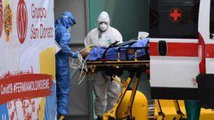 عاملون طبيون ينقلون مريض من سيارة إسعاف تابعة للصليب الأحمر الإيطالي إلى وحدة العناية المركزة التي تم إنشاؤها في مركز رياضي خارج مستشفى سان رافاييل في ميلانو، في 23 مارس 2020 (MIGUEL MEDINA / AFP)