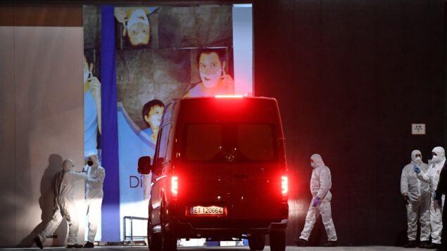 أعضاء وحدة الطوارئ العسكرية في الجيش الإسباني يرتدون بدلات واقية يقفون بينما تصل شاحنة صغيرة إلى مركز التسوق 'قصر الجليد'، حيث تم تحويل حلبة للتزلج إلى مشرحة مؤقتة، 23 مارس 2020 (PIERRE-PHILIPPE MARCOU / AFP)
