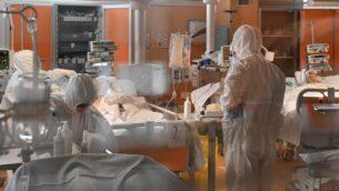 عاملون طبيون في ملابس وقاية يعتنون بالمرضى في وحدة العناية الكثفة الجديدة 3 لحالات الإصابة بفيروس كورونا في مستشفى كاسال بالوكو بالقرب من روما، 24 مارس 2020 (Alberto PIZZOLI / AFP)