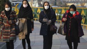 اشخاص يرتدون أقنعة الوجه يمشون على رصيف في غرب طهران، إيران، 29 فبراير 2020. (AP Photo / Vahid Salemi)