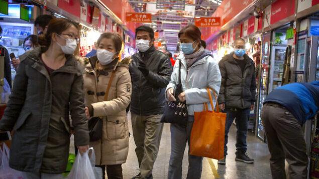 أشخاص يضعون الأقنعة الواقية في أحد أسواق بكين،  14 مارس، 2020. (AP/Mark Schiefelbein)