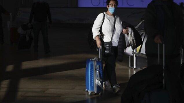 سيدة تضع قناعا واقيا عند وصولها إلى مطار بن غوريون، بالقرب من تل أبيب، 27 فبراير، 2020.  (AP/Ariel Schalit)