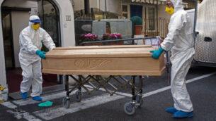 طاقم طبي يرتدي بذلات واقية يحمل تابوت يحتوي على جثة أسونتا باستور (87 عامًا) التي توفيت بعد إصابتها بفيروس كورونا في فندق جاردن في ليغويغليا، شمال غرب إيطاليا، منطقة ليغوريا، 1 مارس 2020 (AP Photo)