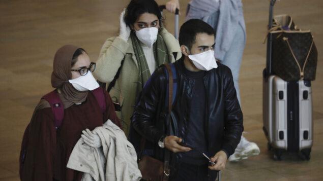 ركاب يرتدون أقنعة للحماية من فيروس كورونا يصلون إلى مطار بن غوريون بالقرب من تل أبيب، 10 مارس 2020 (AP Photo/Ariel Schalit)