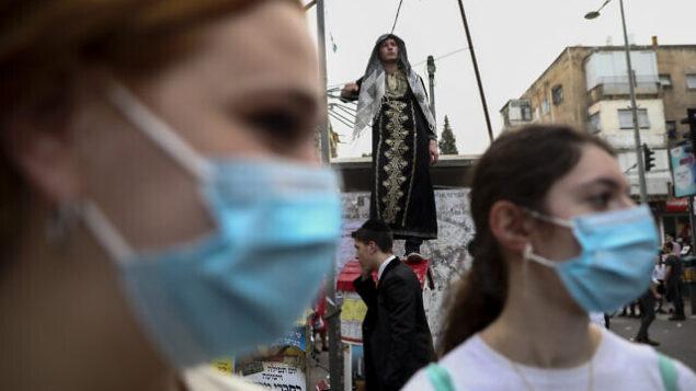 شابتان ترتديان قناعبن خلال الاحتفالات بعيد 'البوريم' في بني براك، إسرائيل، 10  مارس، 2020.  (AP Photo/Oded Balilty)