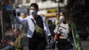 امرأتان تلتقطان صورة سلفي مع أقنعة الوجه في تل أبيب، 15 مارس 2020 (AP / Oded Balilty)