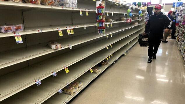 أحد المتسوقين يمر من أمام رفوف خالية حيث يتم عادة وضع الخبز في أحد محلات السوبر ماركت، 15 مارس، 2020، في بوسطن. (AP Photo/Steven Senne)
