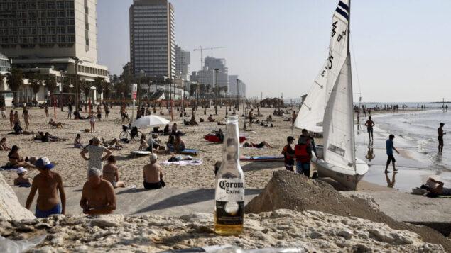 الإسرائيليون يستمتعون بالشاطئ في تل أبيب، 16 مارس 2020 (AP Photo / Oded Balilty)