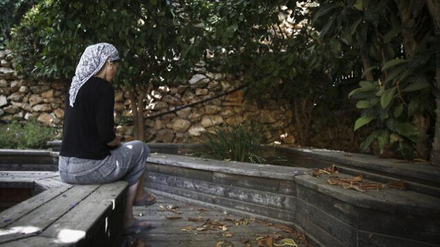 An Orthodox Jewish woman sits in the garden of the abused women's shelter in Beit Shemesh, July 15, 2014. The shelter is a home for women who have suffered physical abuse from their husbands, and their children. Photo by Hadas Parush/Flash90 *** Local Caption *** î÷ìè ðùéí ðùéí îåëåú éìãéí áéú ùîù ãúéåú éäåãéåú