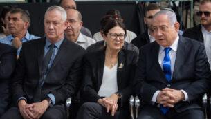 رئيس الوزراء بنيامين نتنياهو (يمين)، زعيم 'أزرق أبيض' بيني غانتس، وكبيرة قضاة المحكمة العليا إستر حايوت في مراسم تأبين الرئيس الراحل شمعون بيريس، في مقبرة جبل هرتسل في القدس، 19 سبتمبر 2019. (Yonatan Sindel / Flash90)