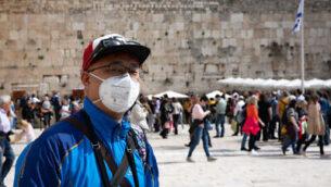 سائح يرتدي قناع بسبب المخاوف من فيروس كورونا خلال جولة عند الحائط الغربي بالبلدة القديمة في القدس، 27 فبراير 2020 (Olivier Fitoussi/Flash90)